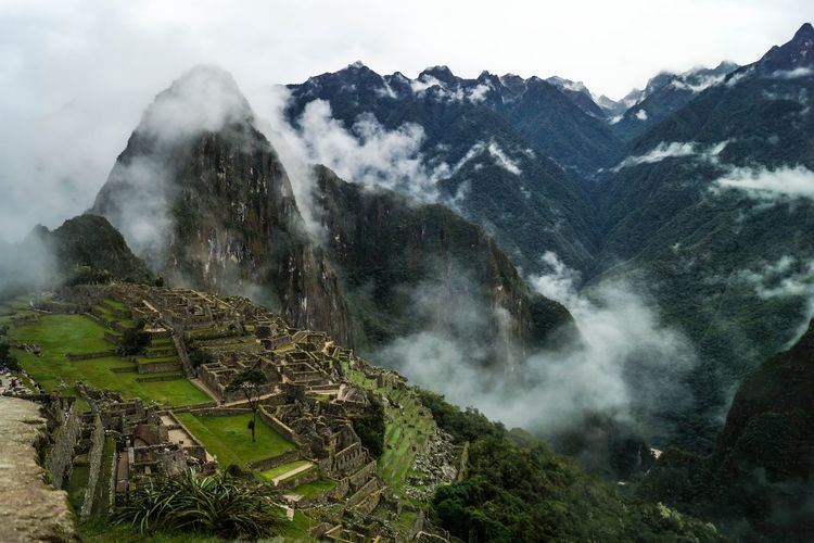 High angle view of machu picchu by mountains during foggy weather
