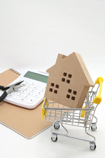 Architecture Home Loan  Renovation Shopping Cart Workshop Business Buy Calculator Cart Consumerism House Indoors  Live Miniature Money No People Purchase Real Estate Remodel Residence Shopping Basket Studio Shot Tools White Background