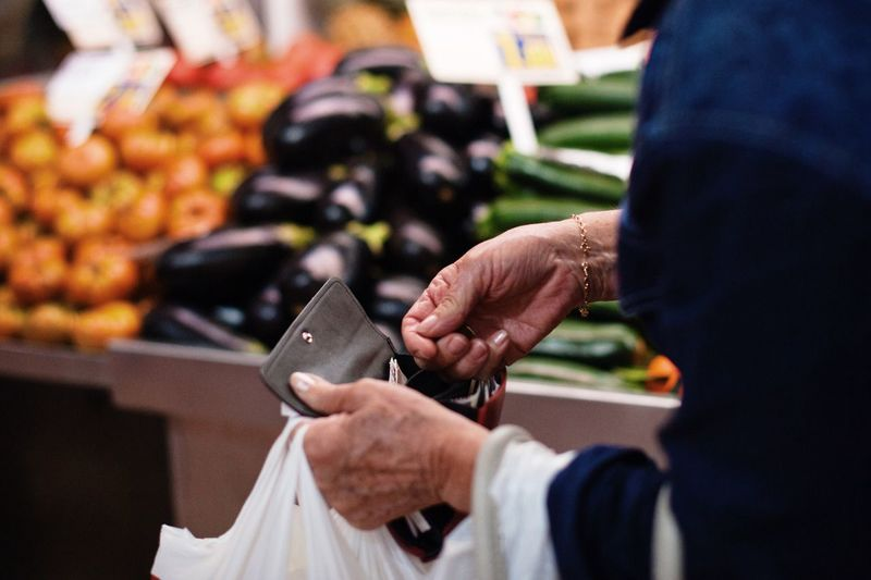 the buyer holds a wallet in the grocery market in Spain Real People Hand Human Hand Holding Focus On Foreground Midsection Human Body Part People Smart Phone Women Lifestyles Wireless Technology Men Two People Portable Information Device Technology Adult Mobile Phone Outdoors