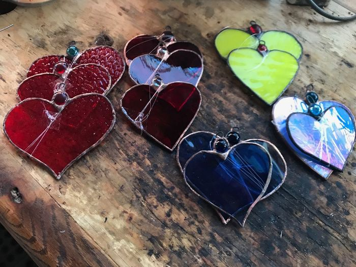 Gifts of Love Stained Glass Heart Hearts Blue Red Purple Iridescent  Yellow Wooden Table Work Table Burnt Wood Window Hangers Pretty Glass Glass Art Design Table High Angle View Close-up Heart Shape Things That Go Together I Love You Valentine Day - Holiday EyeEmNewHere