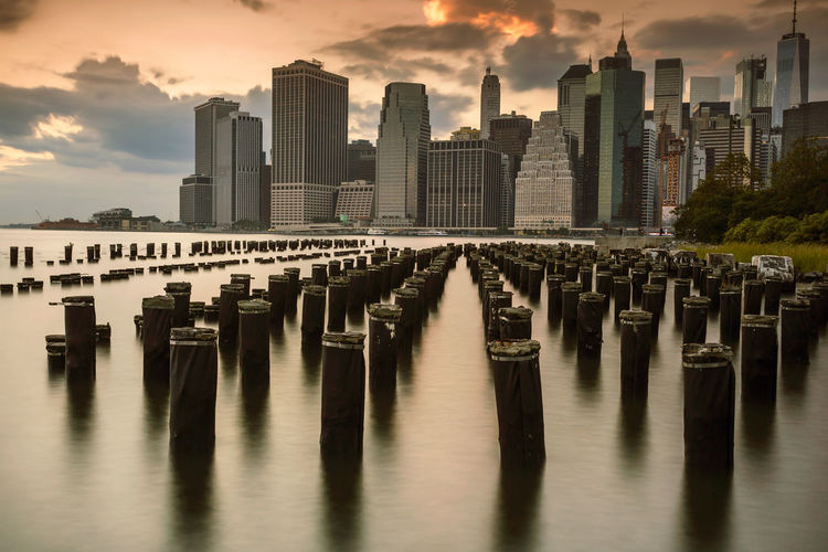 Wooden posts in river against buildings in city during sunset
