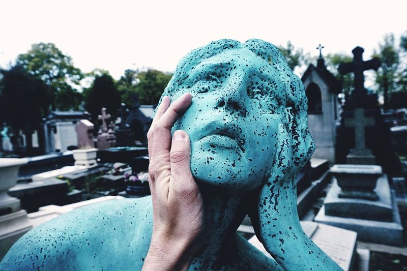 Cropped image of hand touching weathered stone sculpture in pere lachaise cemetery