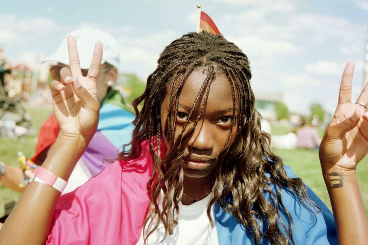Portrait of young woman showing peace signs on sunny day