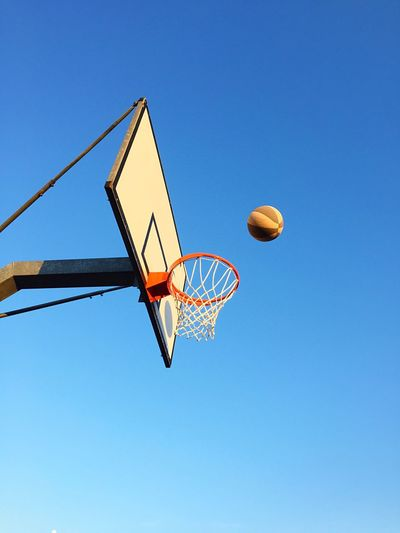 Playing basketball against sky Basketball Hoop Basketball - Sport Blue Low Angle View Sport Copy Space Clear Sky Day Outdoors No People Court Sky Freedom Competition Game Sports Winner Basket Leisure Games Win Ball Net - Sports Equipment Basketball Low Angle View Making A Basket