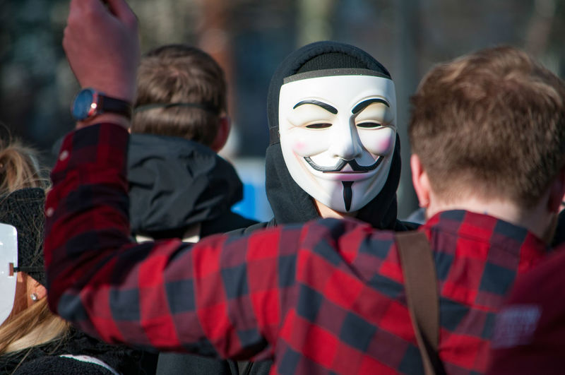 Man wearing mask during protest in city