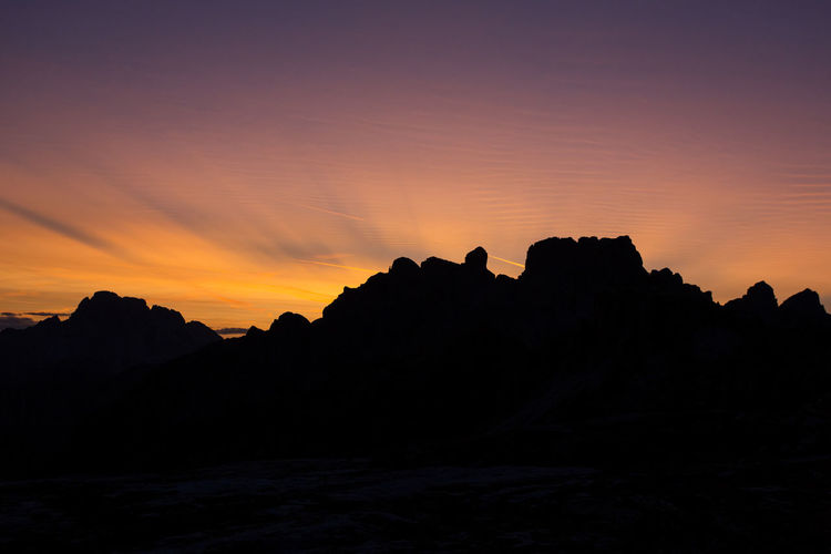 Silhouette mountains against sky at sunset