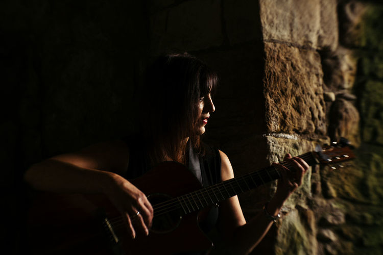 Woman playing guitar by stone wall