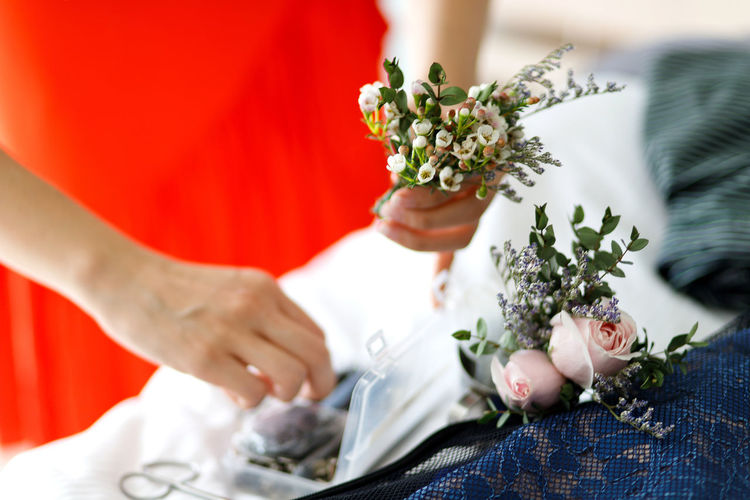 Woman making beautiful flower corsage Flower Adult Plant Women Hand Flower Arrangement Flowering Plant Human Hand Two People Wedding Celebration Bouquet Event Midsection Newlywed People Bride Selective Focus Life Events Corsage Preparation  Florist Professional Art And Craft