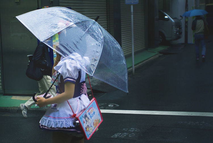 Woman holding umbrella walking on road
