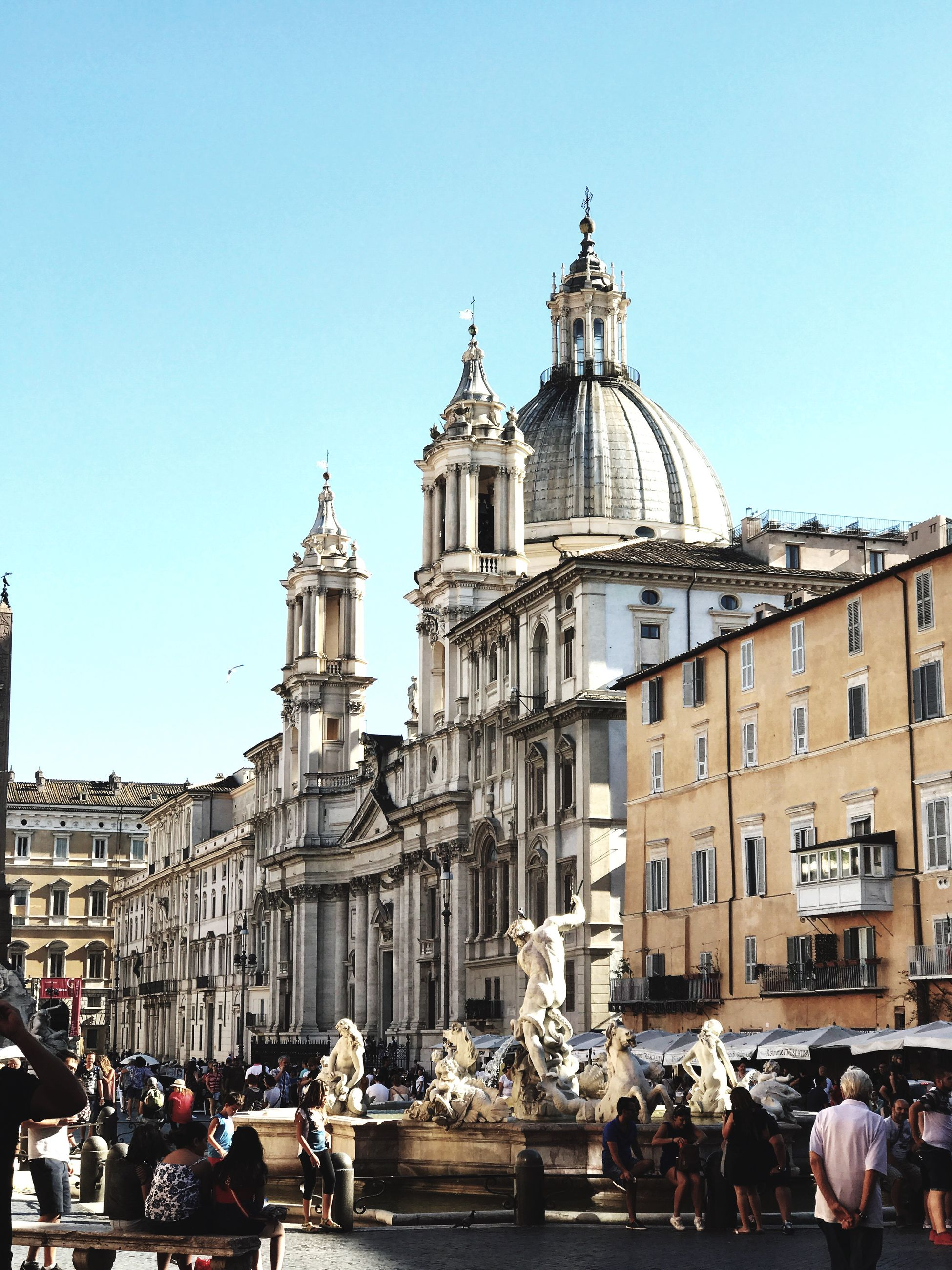 architecture, statue, building exterior, built structure, sculpture, human representation, large group of people, clear sky, art and craft, place of worship, religion, spirituality, history, real people, travel destinations, dome, men, day, outdoors, city, baroque style, sky, people