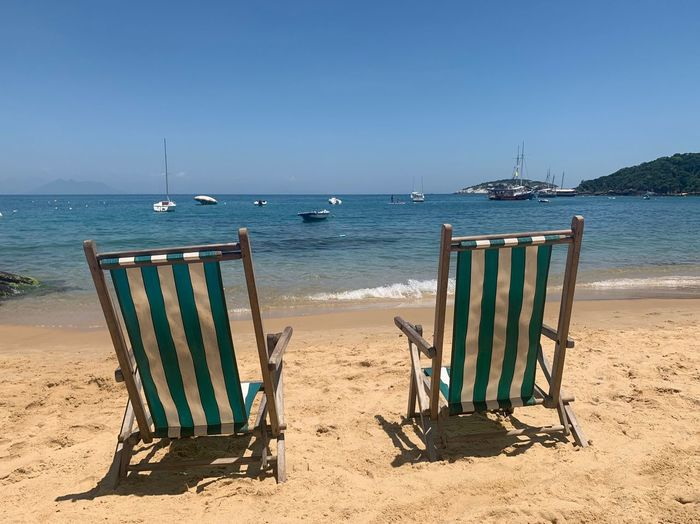 Sun Chair Sea Beach Water Sky Land Sand Nature Tranquility No People Outdoors Day Scenics - Nature Tranquil Scene Beauty In Nature Sunlight Horizon Horizon Over Water Clear Sky Blue
