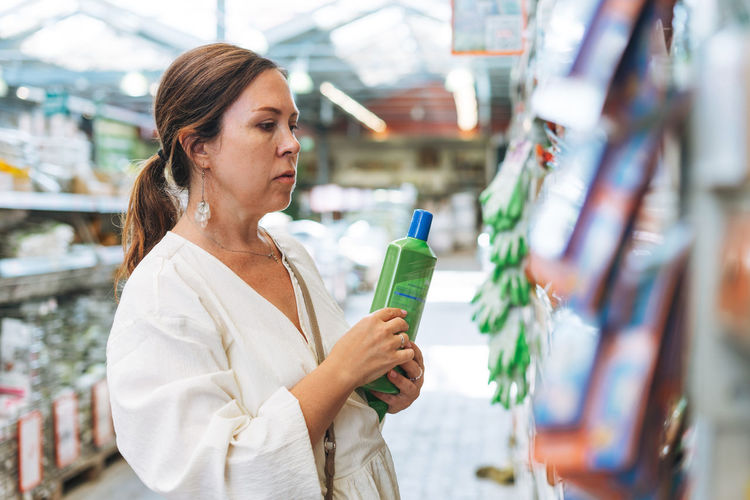 Midsection of woman looking up at store