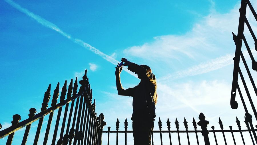 Low angle view of man photographing while standing by railing against sky
