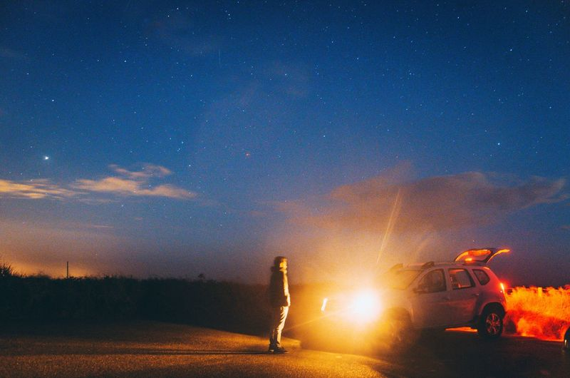 Man standing on road against sky at night