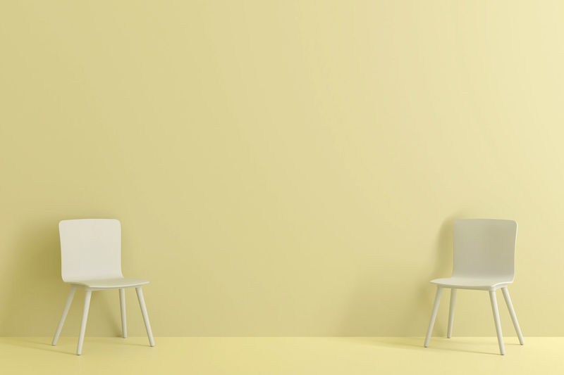 Empty chairs against yellow wall