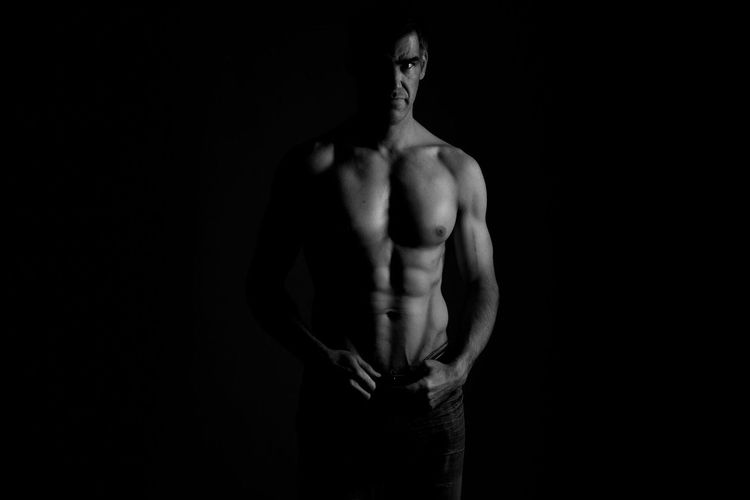 Portrait of shirtless muscular male model standing against black background