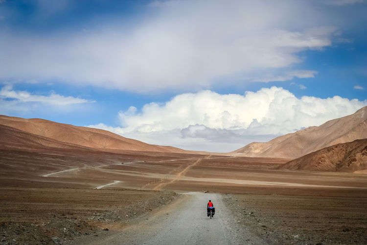 Rear view of person riding bicycle on dirt road against sky