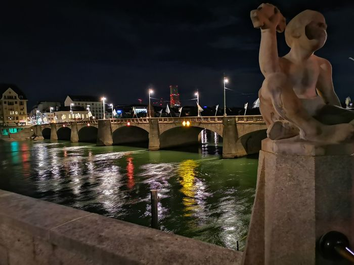 Statue of illuminated bridge over river against sky at night