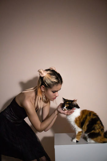 Woman with cat against colored background