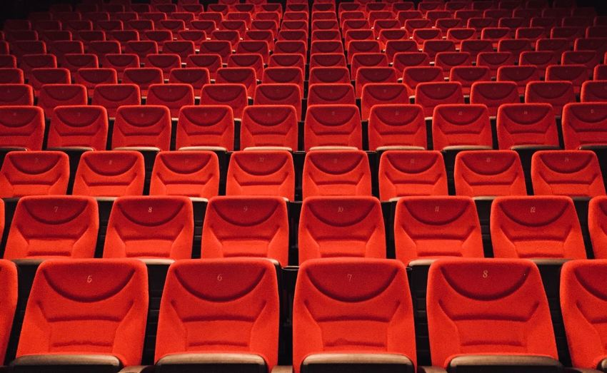 Full frame shot of empty chairs with numbers in movie theater