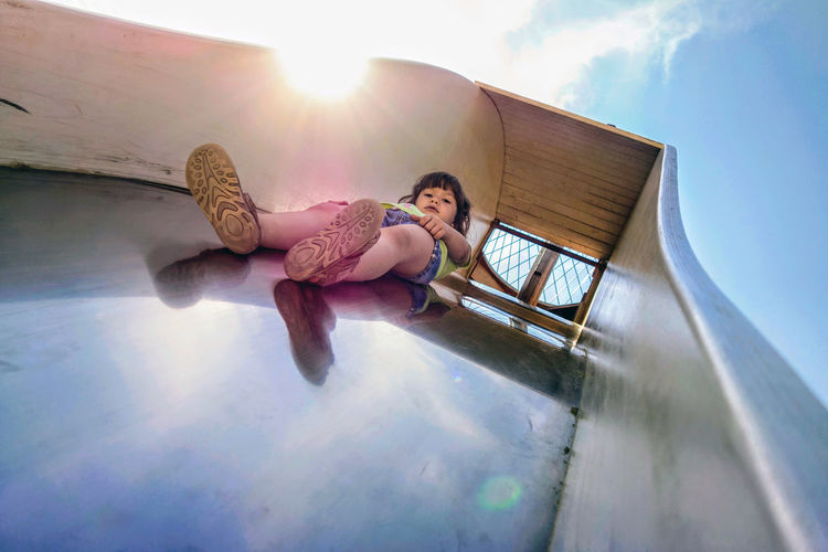 Low angle view of cute girl on slide against sky