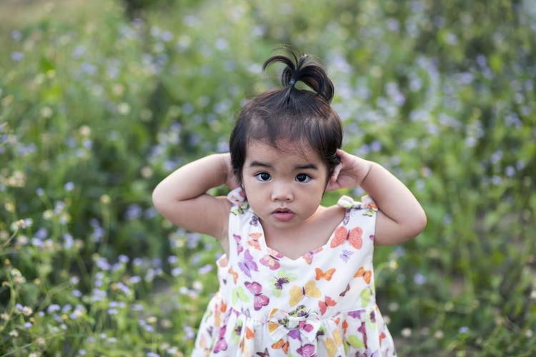 Portrait of cute girl against plants