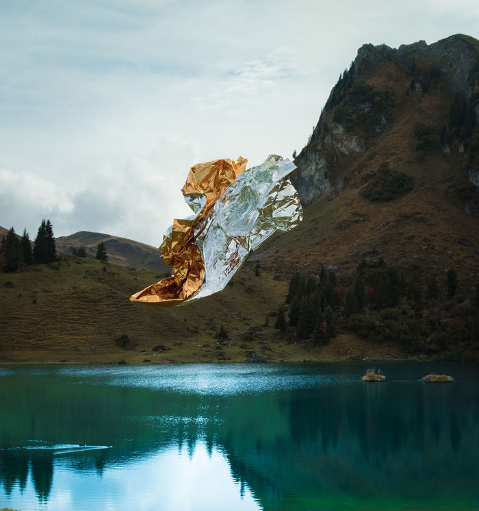 Foil flying over lake by mountain