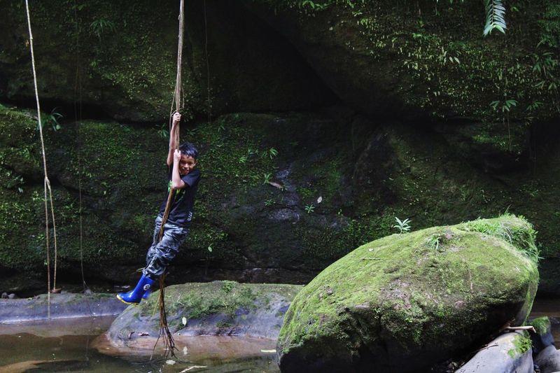 Full length of boy swinging on branch over lake against rocks
