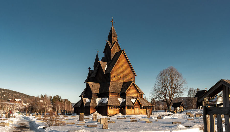 Architecture Built Structure Sky Clear Sky Place Of Worship Religion Building Exterior Belief Building Spirituality Snow Cold Temperature Nature Winter Blue Tree No People Day Spire  Stave Church