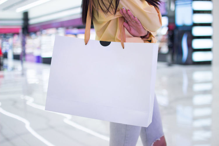 One Person Shopping Women Retail  Store Consumerism Bag Day Lifestyles Shopping Bag Adult Focus On Foreground Customer  Casual Clothing Standing Holding Midsection Shopping Mall Real People Retail Display
