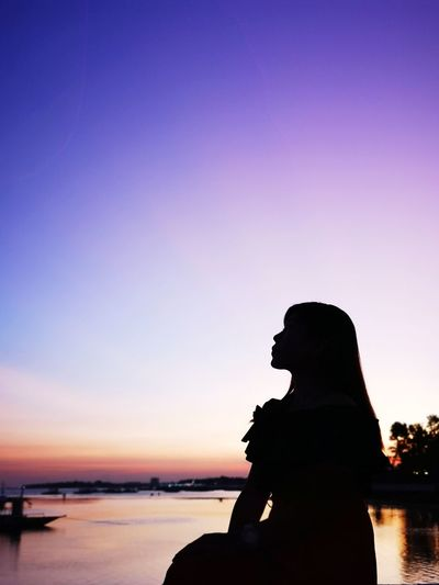 Silhouette woman standing by sea against dramatic sky during sunset