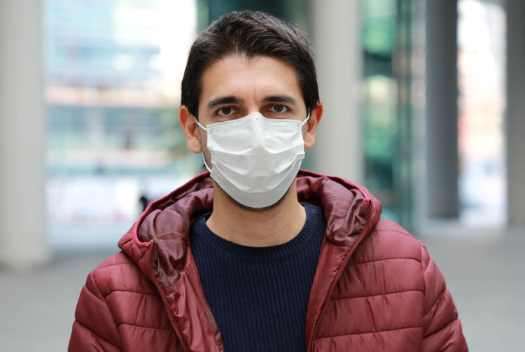 Portrait of mid adult man wearing mask standing outdoors