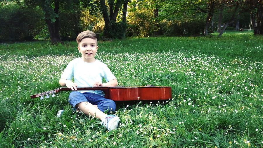Portrait of boy with guitar sitting on field