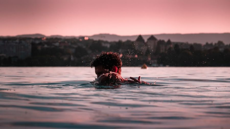 Woman swimming in pool against sky during sunset