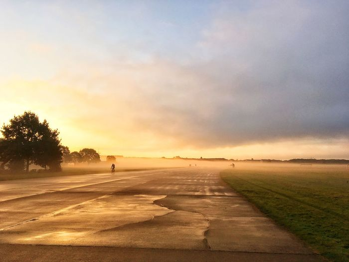 Sunset Sky Nature Tranquil Scene Beauty In Nature Landscape Scenics Outdoors Tranquility Cloud - Sky The Way Forward Sunlight Road Tree Real People Day Tempelhofer Feld Tempelhof Airport Done That. Discover Berlin Premium Collection