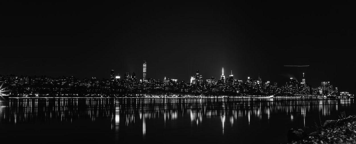 Scenic View Of Illuminated Cityscape And Lake Against Sky At Night