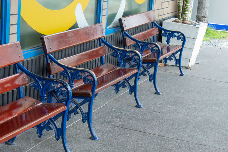 High angle view of empty benches on footpath