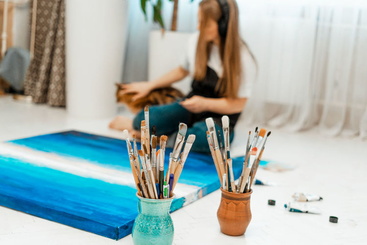 Woman painting on canvas at home