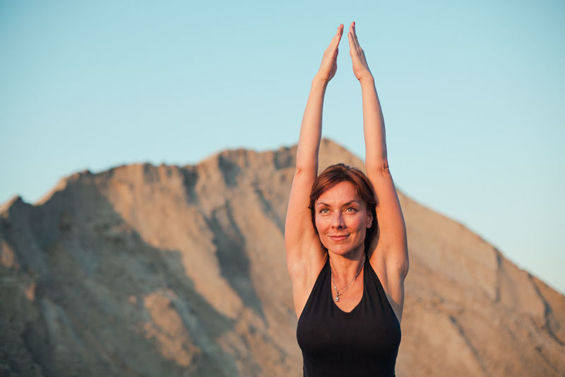 portrait of a young woman practicing yoga Sand Sandy Area Background Lifestyles Arms Raised Exercising Sky Leisure Activity Women Front View Healthy Lifestyle Relaxation Exercise Young Adult Nature Wellbeing Outdoors Yoga Fit Care Balance Portrait Energy Centered Confidence
