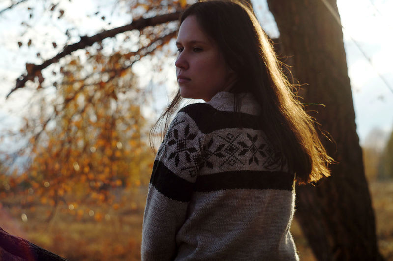 Beautiful young woman against tree