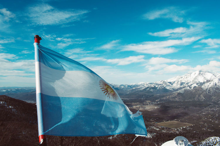 Flag on snowcapped mountain against blue sky