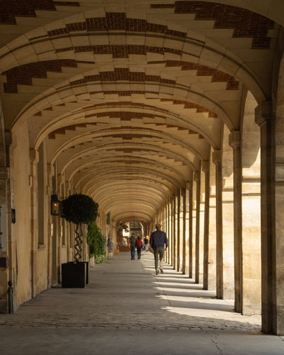 EyeEm Arcade Arch Architectural Column Architecture Building Built Structure Ceiling Colonnade Corridor Day Diminishing Perspective Direction Full Length History In A Row Incidental People Indoors  Men Rear View Streetphotography The Past The Way Forward Walking