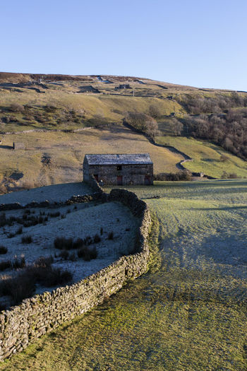 A stone field barn and dry stone wall near Keld, North Yorkshire in the Yorkshire Dales National Park Barn Copy Space Dry Stone Wall Frost Winter Yorkshire Dales Yorkshire Dales National Park Architecture Clear Sky Day Environment Field Grass Industry Land Landscape Mine Nature No People Non-urban Scene Outdoors Plant Pollution Scenics - Nature Sky