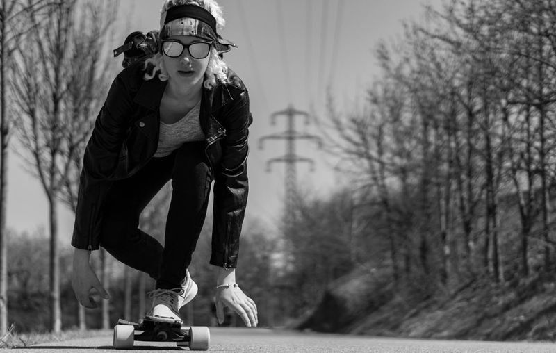 Full Length Portrait Of Young Woman Skateboarding On Road