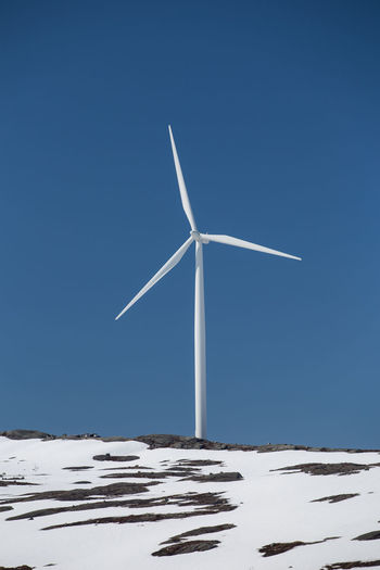 Wind turbine on snowy landscape against clear sky