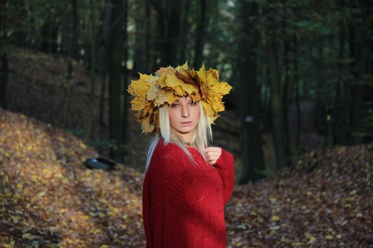 Portrait of woman wearing wreath while standing in forest