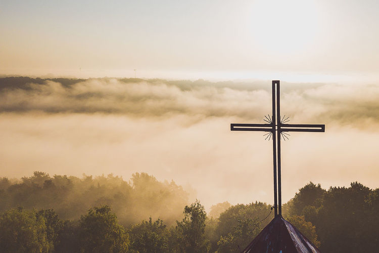 Cross overlooking trees covered with clouds