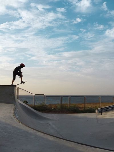 Young Man Performing Stunt Against Cloudy Sky At Skateboard Park