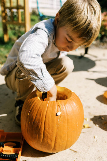 Full length of boy holding pumpkin against stone wall during halloween