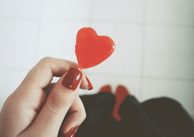 Cropped Hand Of Woman Holding Heart Shape Candy